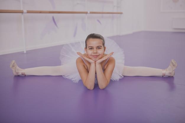 ダンススクールで運動する魅力的な少女バレリーナ Premium写真