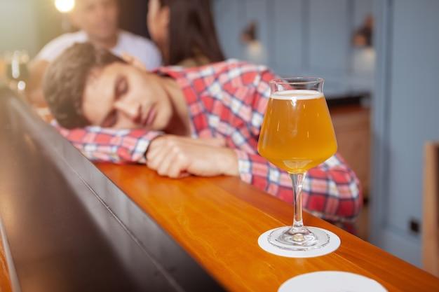 Красивый молодой человек пьет в пивной паб Premium Фотографии
