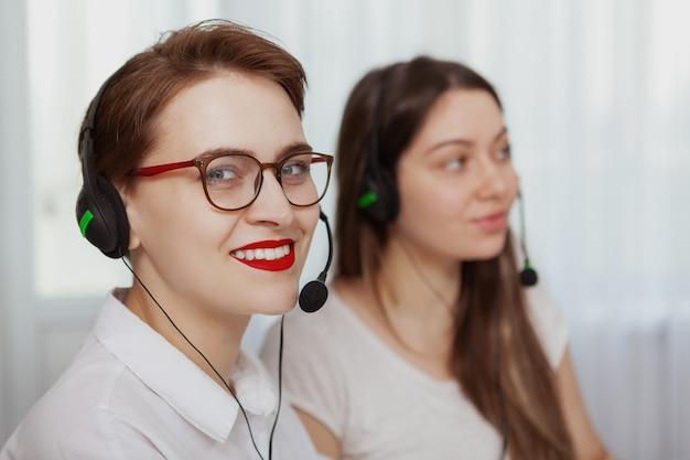 Две женщины-операторы колл-центра работают на компьютере Premium Фотографии