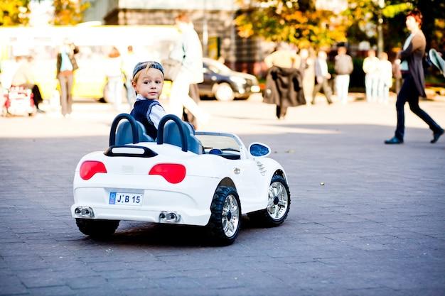 ねえ、そこには何がありますか?かわいい少年が最初の車を運転する 無料写真