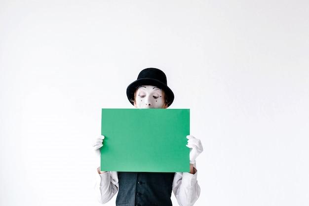 マミは彼の顔の前に緑の紙を保持 Premium写真