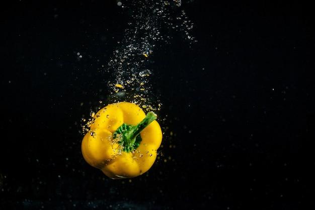 泡が水の中に落ちる黄色の胡椒の周り 無料写真