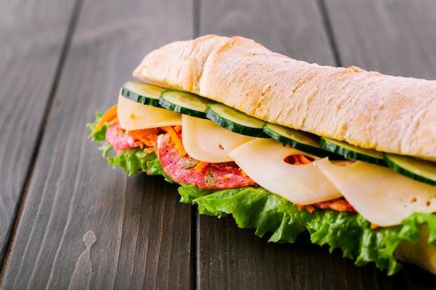キュウリ、チーズ、サラミ、グリーンサラダが入った地中海風のパンのサンドイッチ 無料写真