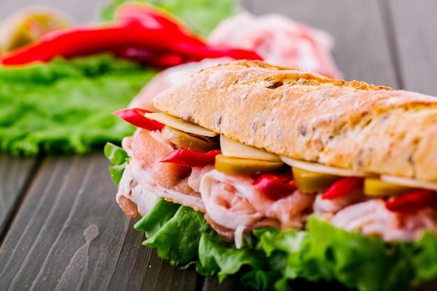 ジューシーな赤い唐辛子は、サンドイッチの全粒粉のパンの下から見える 無料写真
