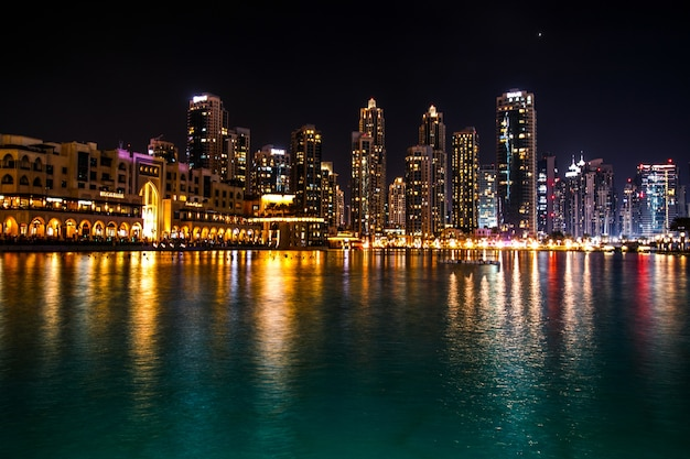 輝くドバイの高層ビルが夜の水に映ります 無料写真