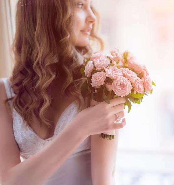 花嫁は窓の上に座って彼女の肩の前に少しピンクの花束を保持しています Premium写真
