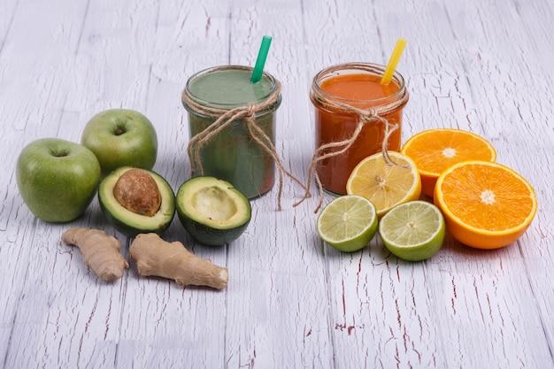 Зеленые и оранжевые коктейли детоксикации на белом столе с фруктами и овощами Бесплатные Фотографии