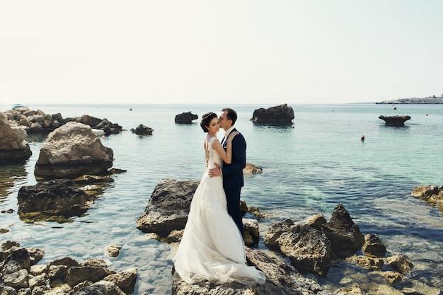 花婿は海の上の岩の上にキスします 無料写真