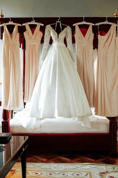 Великолепное свадебное платье и бежевые халаты для подружек невесты висят над плохими Бесплатные Фотографии