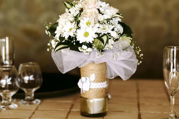 シャンペンとブランデーのテーブルの上に、デイジーとピンクのバラの緑色の花束と緑色の美しい装飾花瓶。 無料写真