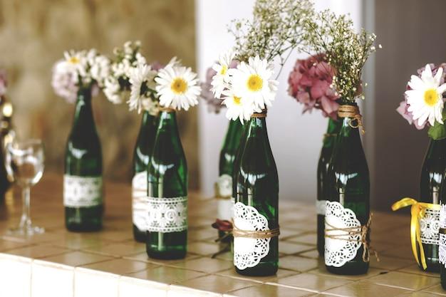 白いデイジーとガラスの透明な背の高い緑色のボトルの紫色の水晶、花瓶の装飾的な花束。 無料写真