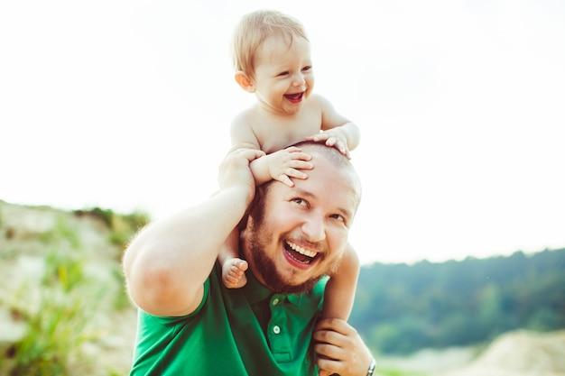 «короткошерстный отец, несущий малыша на плечах» Бесплатные Фотографии
