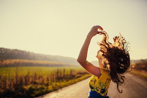 バックグラウンドで道路に彼女の髪を持ち上げて女 Premium写真