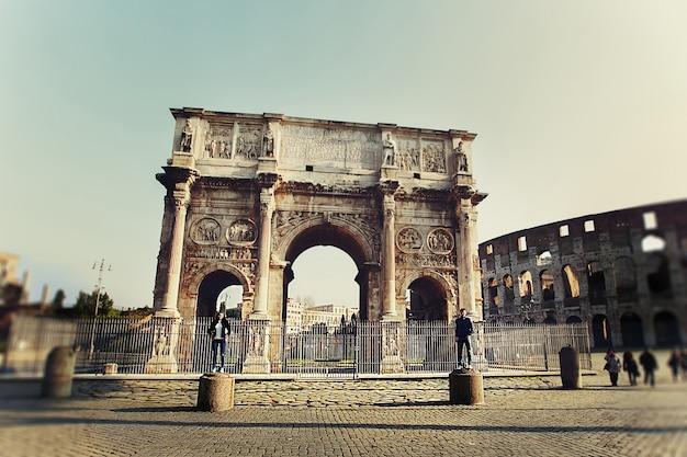 コンスタンティヌスのアーチの近くの柱に立っている二人の人 無料写真