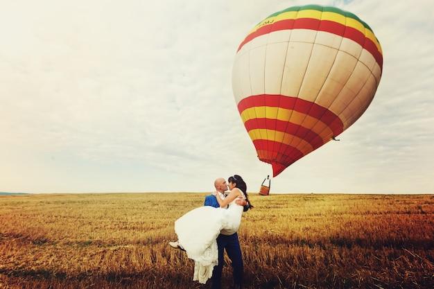 風が風船を吹き飛ばす間、新郎は腕の中に花嫁を保持する 無料写真