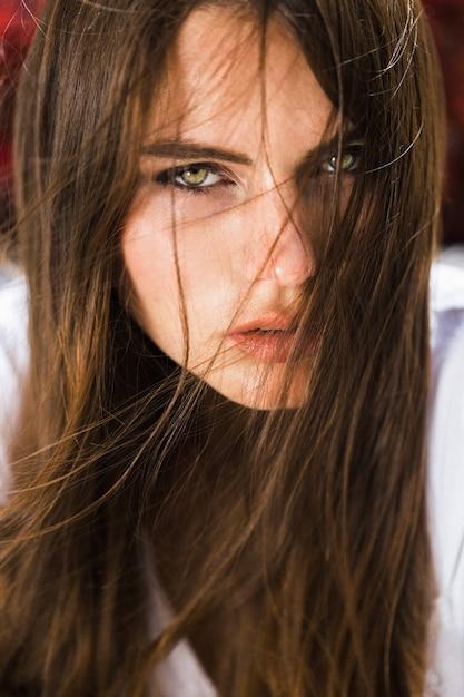 見事な緑色の目の女は、赤い花の前に座っている 無料写真