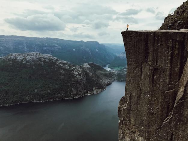 黄色のジャケットを持つ男が岩の上にポーズをとる 無料写真