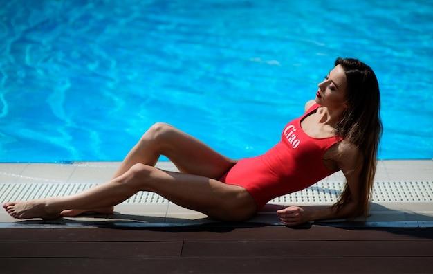 青いスイミングプールで赤い水着の女の子が嘘 無料写真