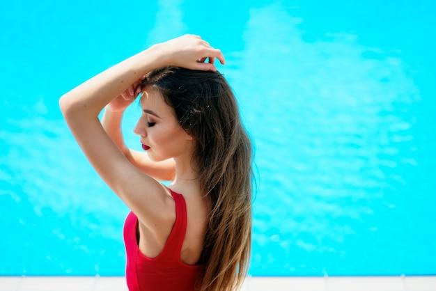 赤いスーツの女の子は青いプールで座っています 無料写真