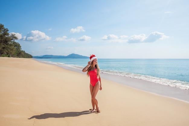 ビーチで赤い水着とサンタクロースの帽子の若い女性 Premium写真