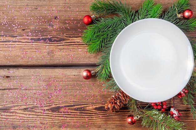 Белая рождественская тарелка с сосновыми ветками с елочными украшениями на деревянном фоне с блестками Premium Фотографии