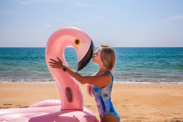 青い水着で若くてセクシーな女の子は青い水着で膨脹可能なピンクのフラミンゴにキスします。 Premium写真