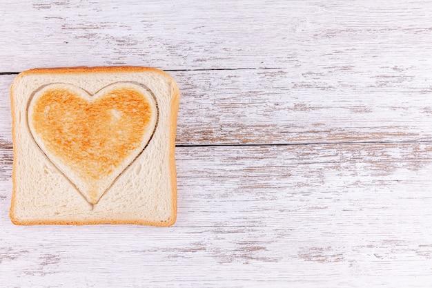 トーストしたパン刈り取ら心、幸せなバレンタインデーのコンセプト、愛と朝の食事 Premium写真