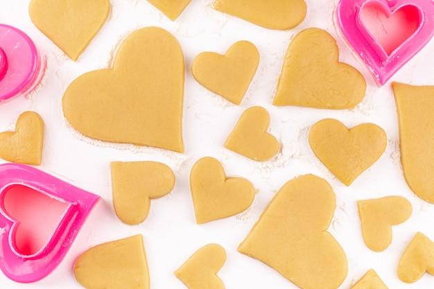 ピンクのクッキーカッターと小麦粉で生の自家製ハート型クッキー Premium写真