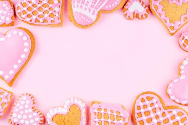 ピンクの背景に手作りの装飾が施されたハート型のクッキーからフレーム Premium写真