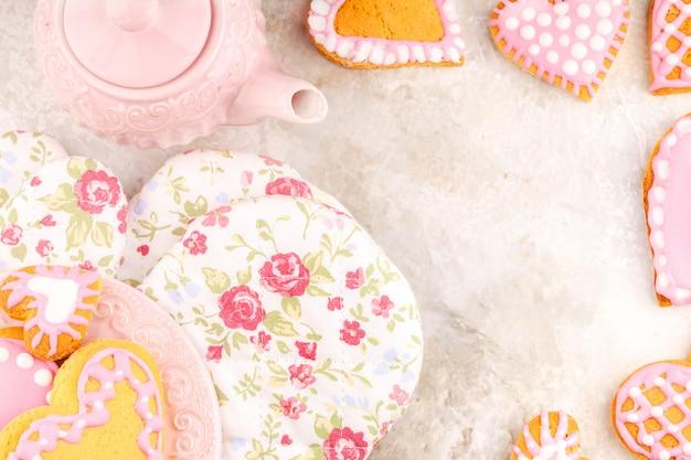 ピンクのティーポット、フラワーグローブ、手作りの艶をかけられたハート型のクッキーのプレート Premium写真