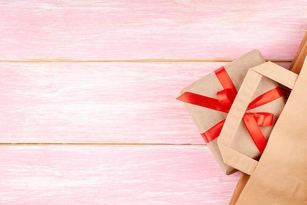 クラフトペーパーバッグとギフトボックスに赤いリボンの弓とピンクの背景にハート Premium写真