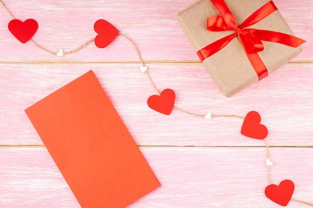 リボンリボン、赤いバレンタインブランクカード、ジュートロープ上の心のギフトボックス Premium写真
