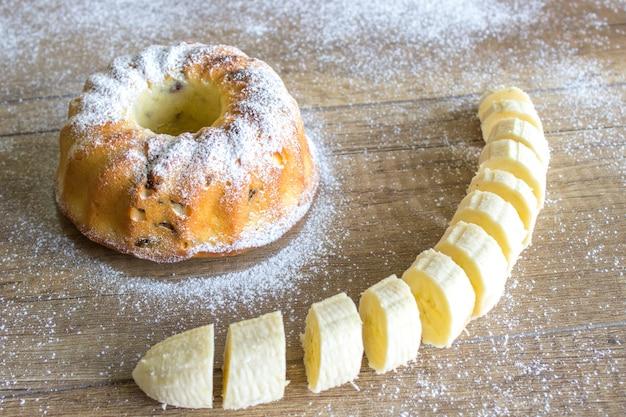 粉砂糖をまぶした木製のテーブルにバナナケーキと熟したバナナ Premium写真