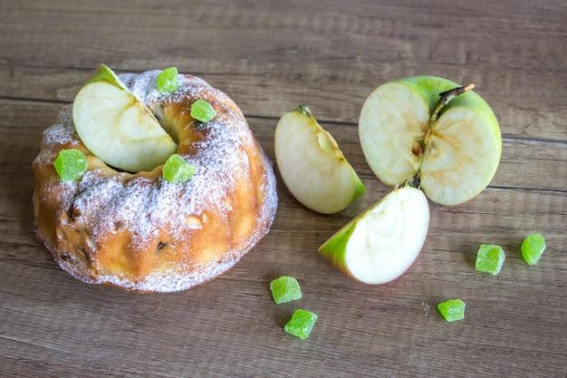 アップルケーキと木製のテーブルの上の緑のリンゴ Premium写真