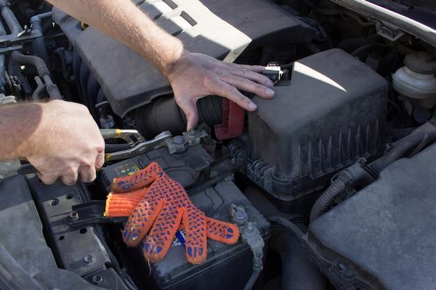 職場のメカニック、オープンフードの下で車のエンジンの詳細を閉じます。 Premium写真