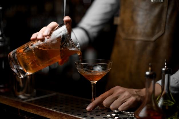 バーテンダーがストレーナーからアルコールカクテルを注ぐ Premium写真