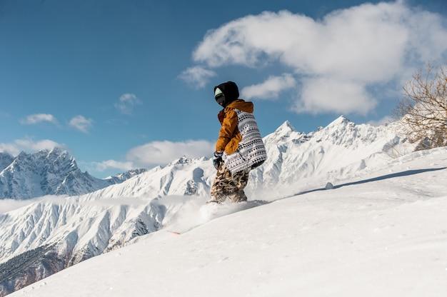 Женский сноубордист в спортивной одежде верхом на склоне горы Premium Фотографии