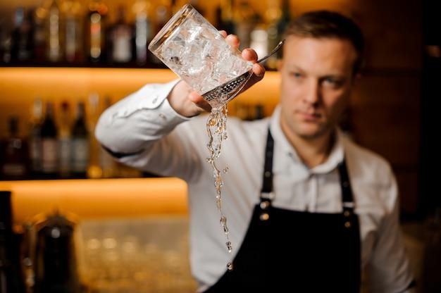 アイスキューブとグラスから水を注ぐバーテンダー Premium写真