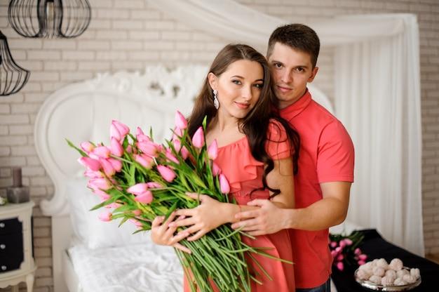 ピンクのチューリップの大きな花束と美しい、若いカップルの肖像画 Premium写真