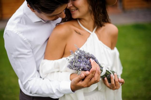 花の花束と白いドレスで笑顔の花嫁を抱いて白いシャツを新郎します。 Premium写真