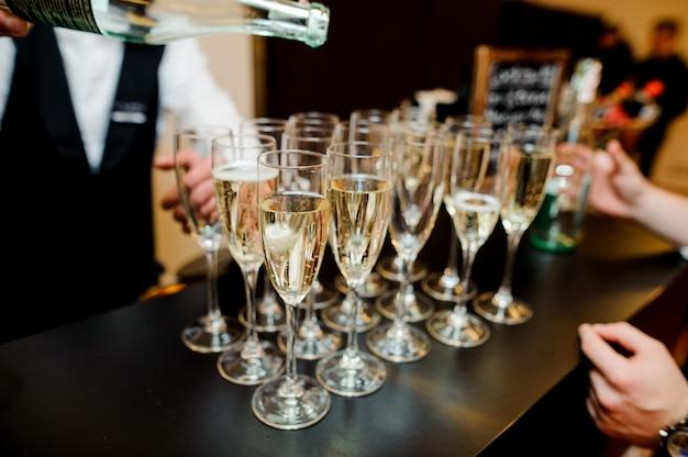 バーでグラスにシャンパンを注ぐバーマン Premium写真