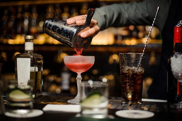 グラスに新鮮なアルコールカクテルを注ぐバーテンダー Premium写真