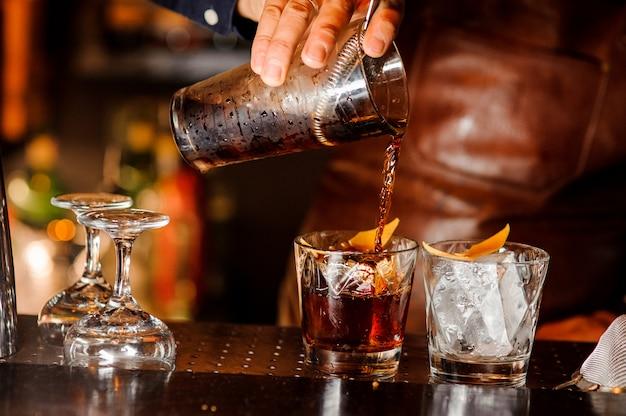 バーテンダーがアルコール飲料をグラスに注ぐ Premium写真