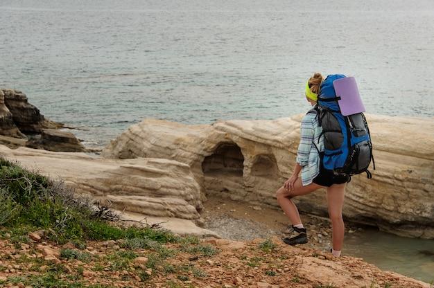 海を見てハイキングバックパックを保持している岩の上に足で立っている女の子 Premium写真