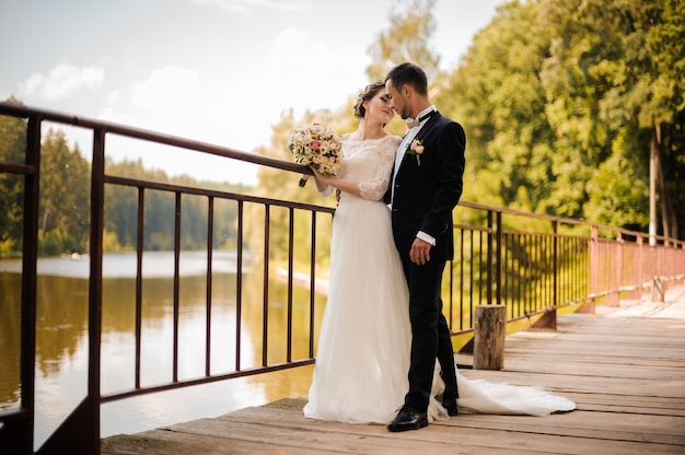 Молодая и привлекательная свадебная пара на мосту Premium Фотографии