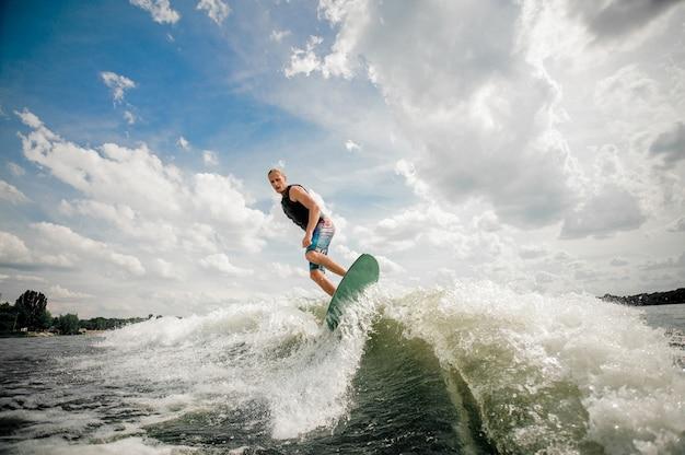 背の高い男が空を背景に川を下ってボードでウェイクサーフィン Premium写真