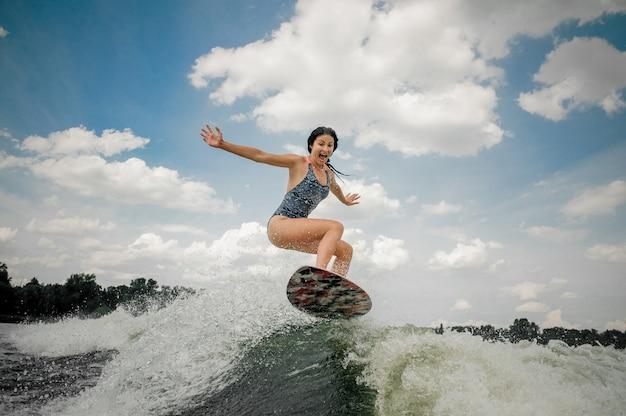 川でウェイクサーフィンボードにジャンプする若い女性の叫び Premium写真