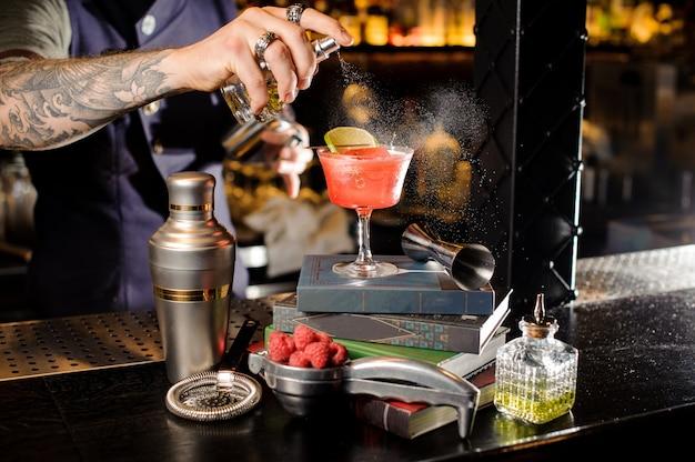 本に配置された赤い甘い夏のカクテルをグラスに泥炭ビターを噴霧バーテンダー Premium写真