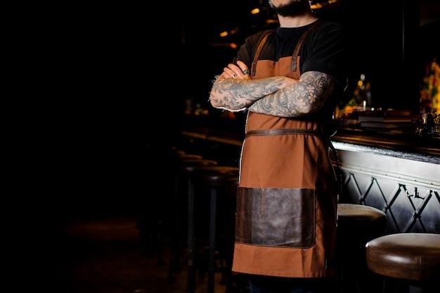 Бармен с татуировкой на руках одет в коричневый фартук Premium Фотографии