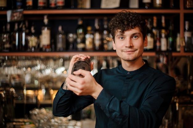 アルコール飲料を振って若いカーリー笑顔バーテンダー Premium写真